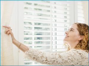 Девушка смотрит на чистые шторы после химчистки клининговой компании
