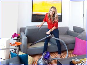 девушка убирается в квартире и пылесосит мебель