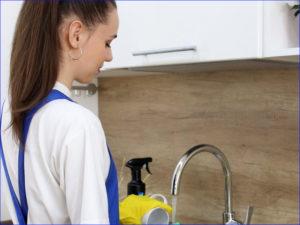 Клинер моет посуду на кухне